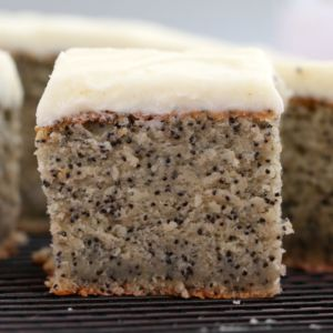 A side view of a cut square of banana and poppy seed cake with white frosting on top