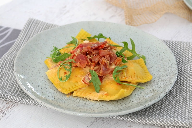 Ravioli squares with a creamy sauce served on a grey plate, and topped with crispy prosciutto and rocket