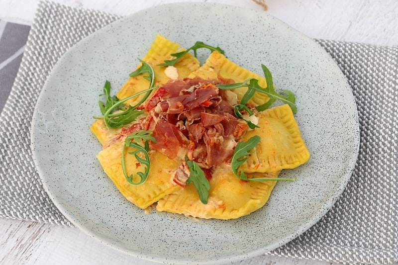 A grey bowl with a small serve of ravioli with a creamy sauce, topped with crispy prosciutto and rocket leaves