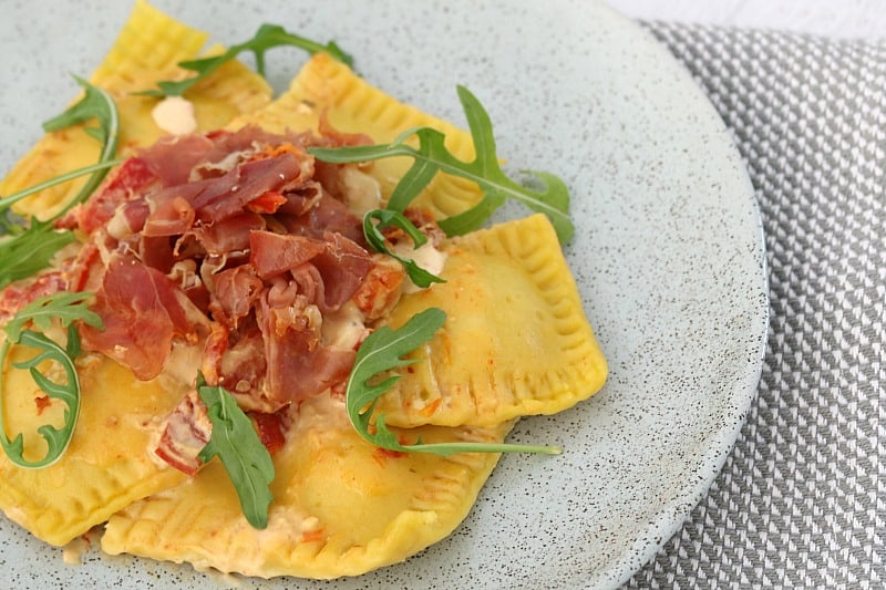 A close up of ravioli with a creamy sauce topped with crispy prosciutto and rocket and served on a grey plate