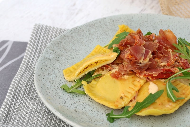 Crispy prosciutto and rocket on top of ravioli pieces served in a grey bowl