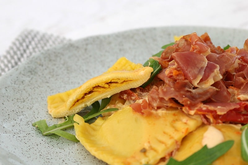 A serve of ravioli with prosciutto and rocket, with one piece split to show a pumpkin filling