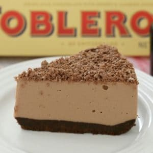 A piece of chocolate cheesecake on a white plate, decorated with grated chocolate in front of a box of Toblerone