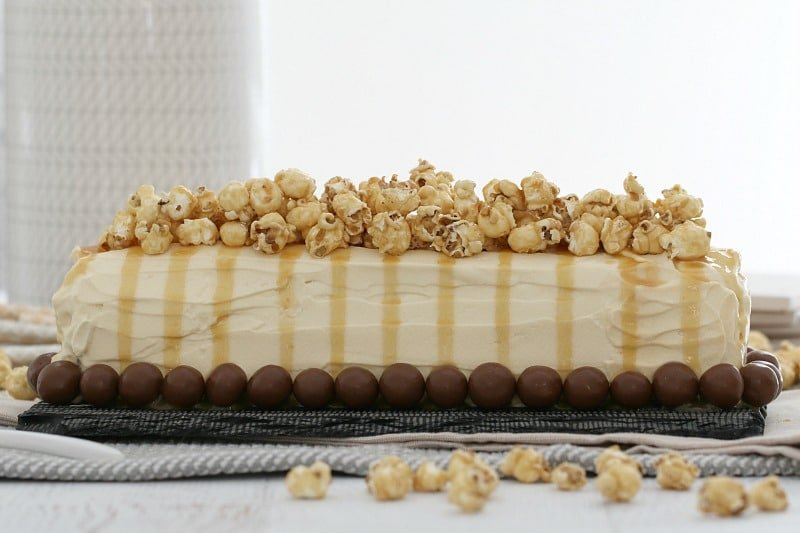 A side view of a cream covered log cake, Malteser balls around the base and caramel sauce drizzled over popcorn on the top