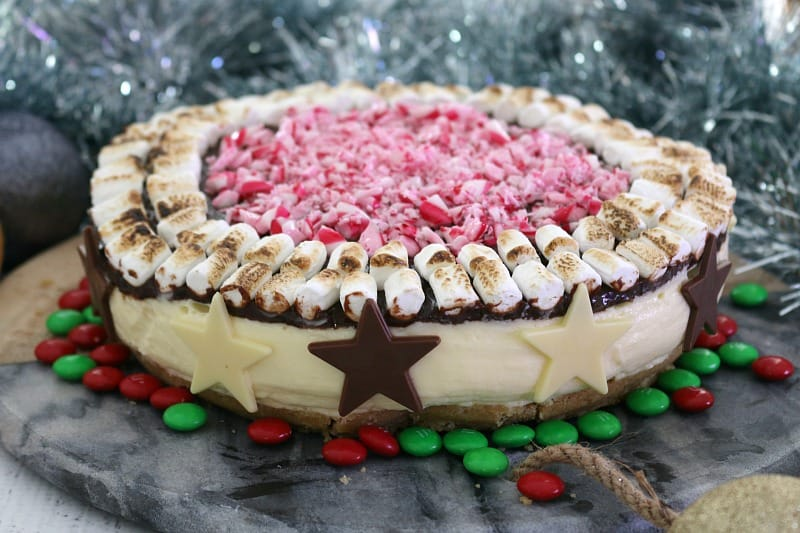 A no-bake S'mores Christmas Cheesecake, decorated with toasted marshmallows, crushed candy canes, chocolate stars and red and green M&M's.