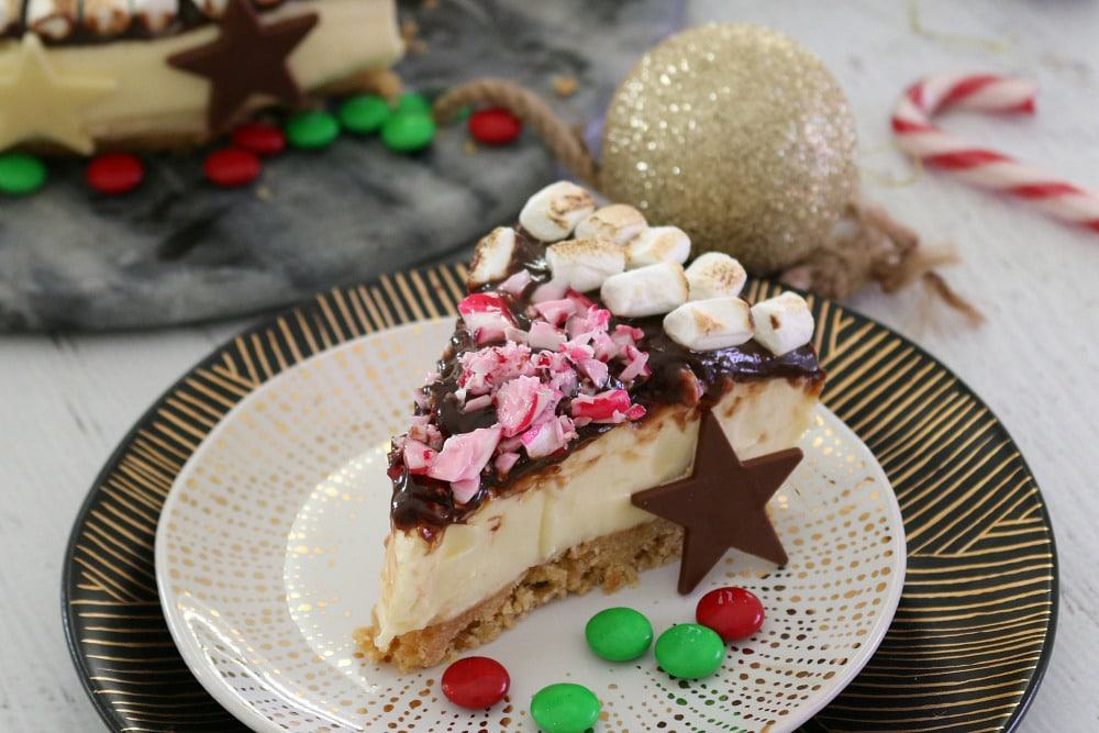 A slice of S'mores Christmas Cheesecake, with a chocolate star and red and green M&M's, on a plate