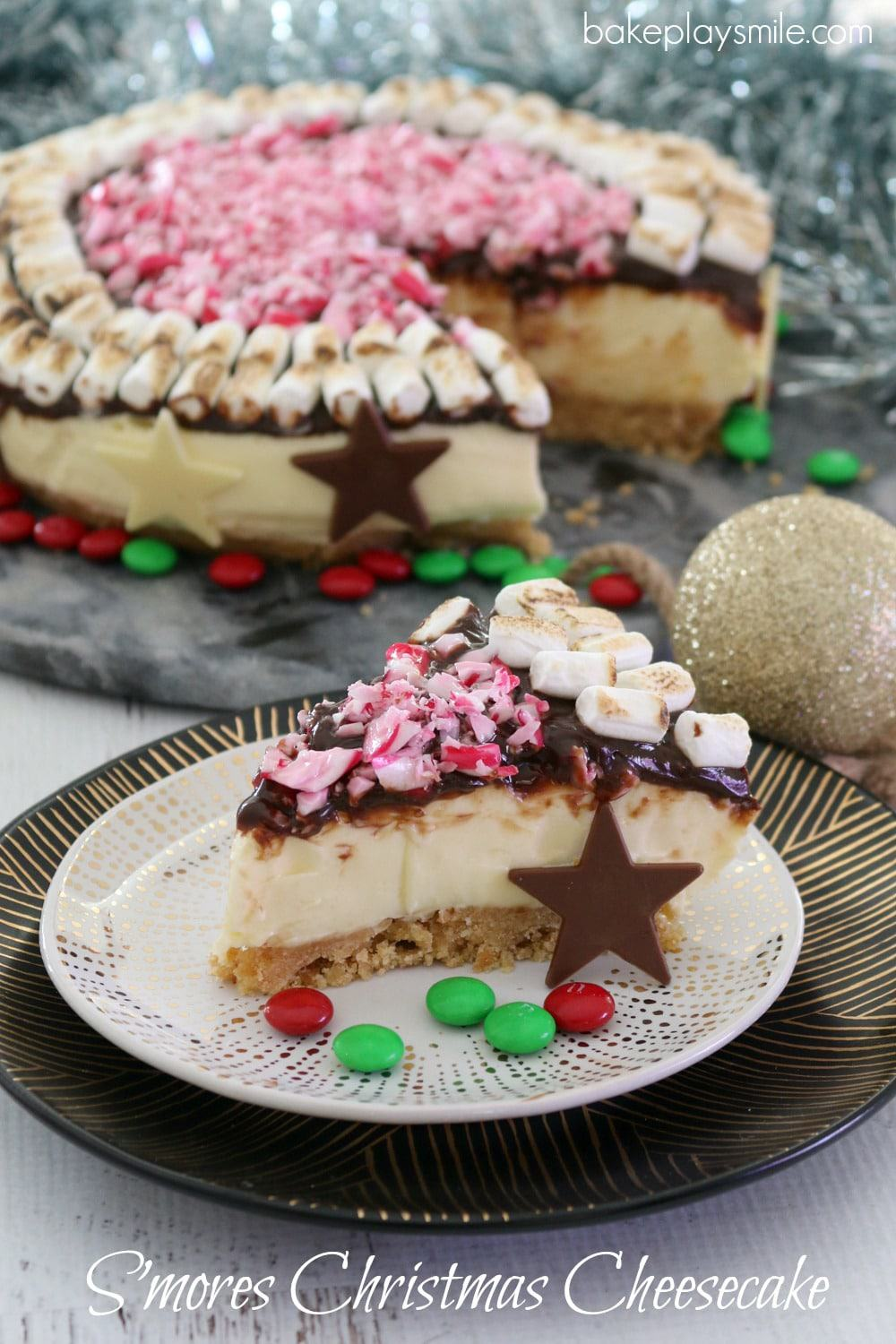 A slice of S'mores Christmas Cheesecake, decorated with toasted marshmallows and crushed candy canes, on a plate