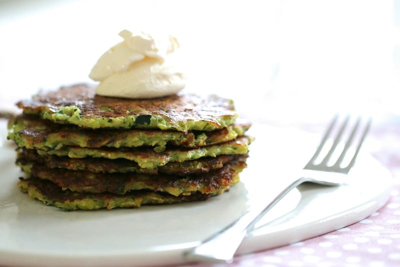 A stack of six thin vege fritters with a dollop of sour cream on top, served on a plate with a fork beside