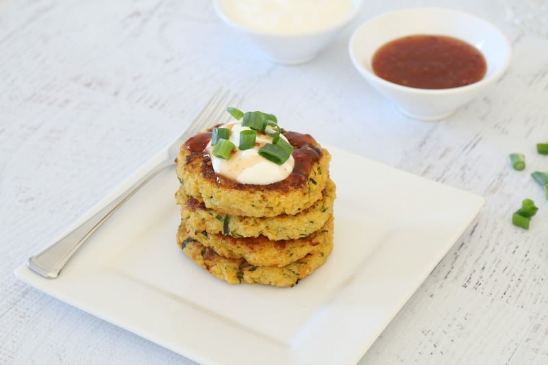 Four vege fritters stacked on a white plate, with a dollop of sour cream on top and a bowl of relish nearby