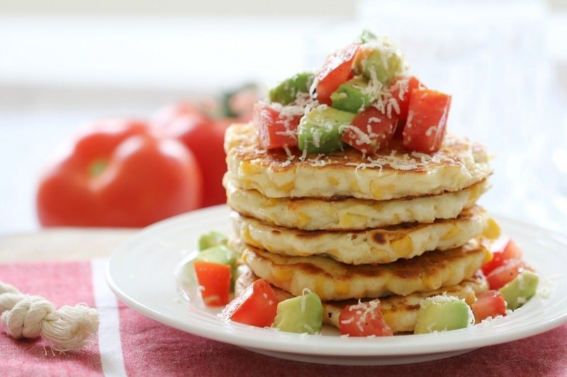 A stack of corn fritters served with a chunky tomato and avocado salsa on top