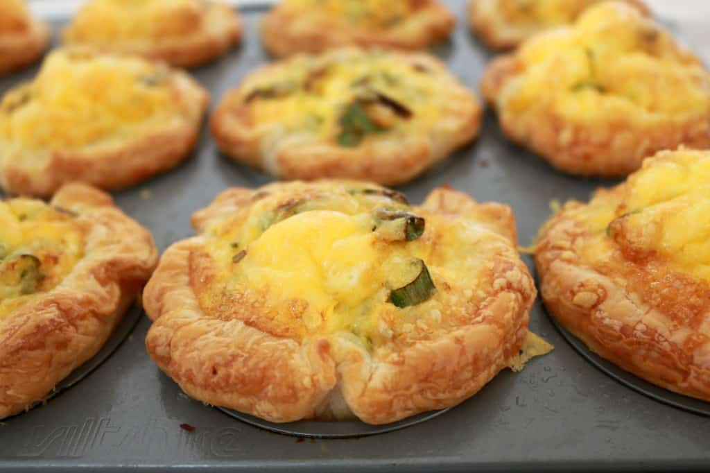 A muffin tray of baked mini pastry quiches filled with ham and corn