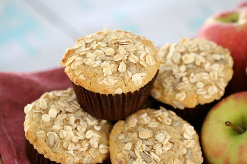 Muffins in brown baking cases topped with oats and stacked in a pile