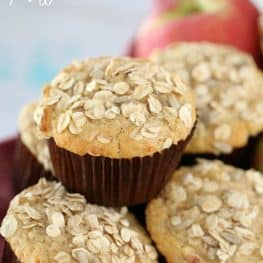 A pile of muffins in brown muffin cases with oats sprinkled on top
