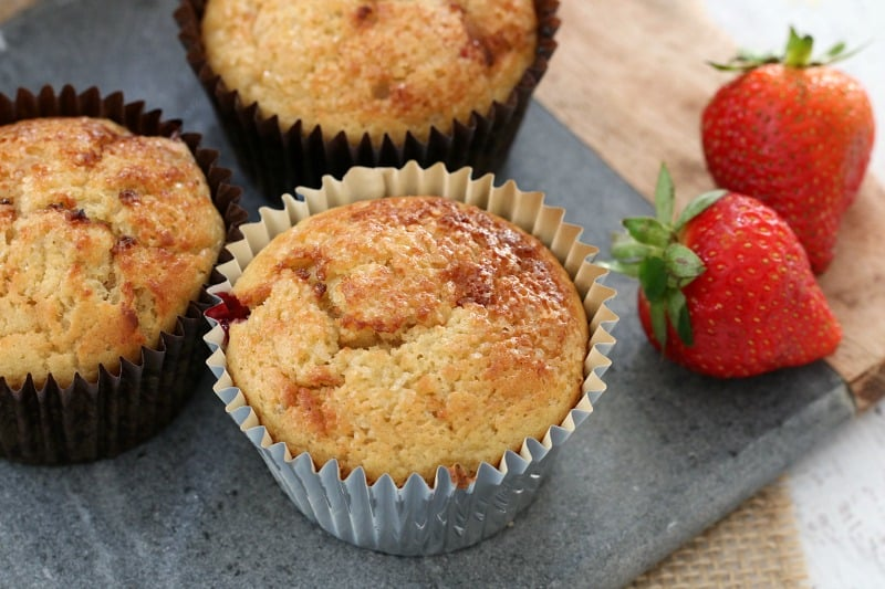 Three muffins in paper muffin cases on a bench with fresh strawberries alongside