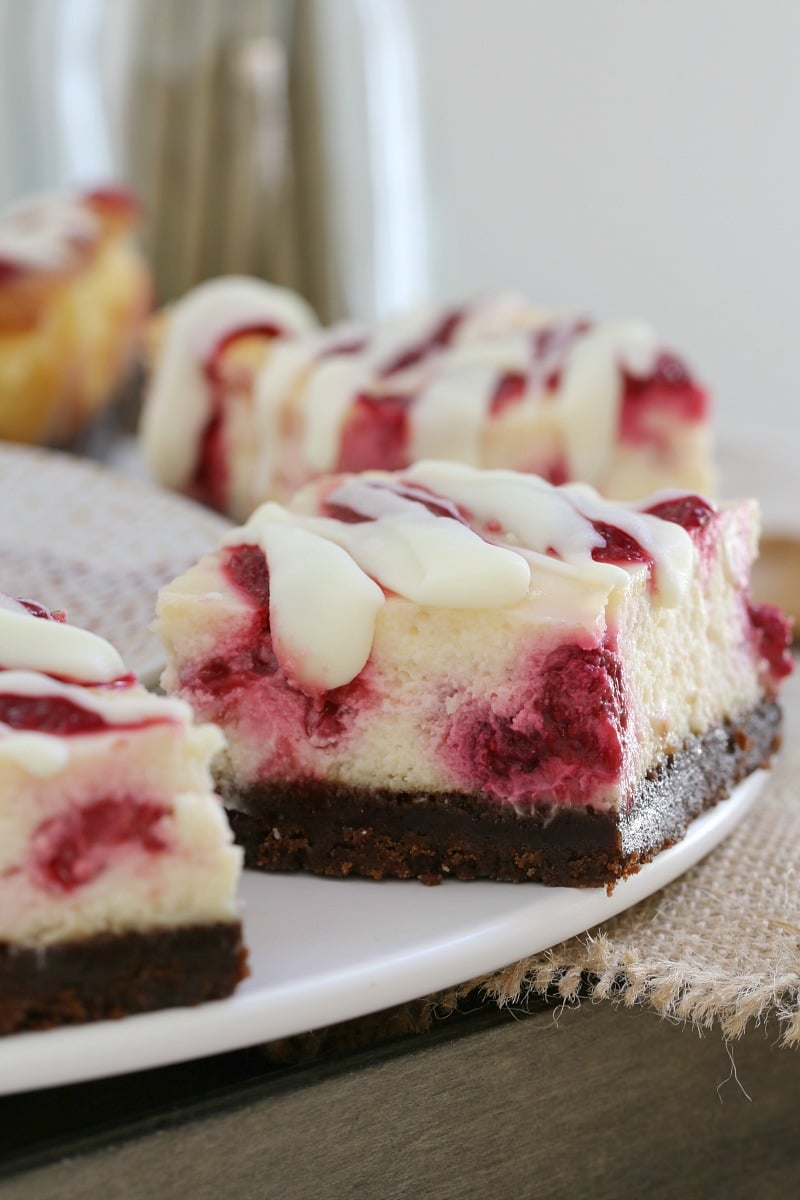 A close up cheesecake squares with a chocolate base, a filling with raspberries swirled through, and white chocolate drizzled over the top