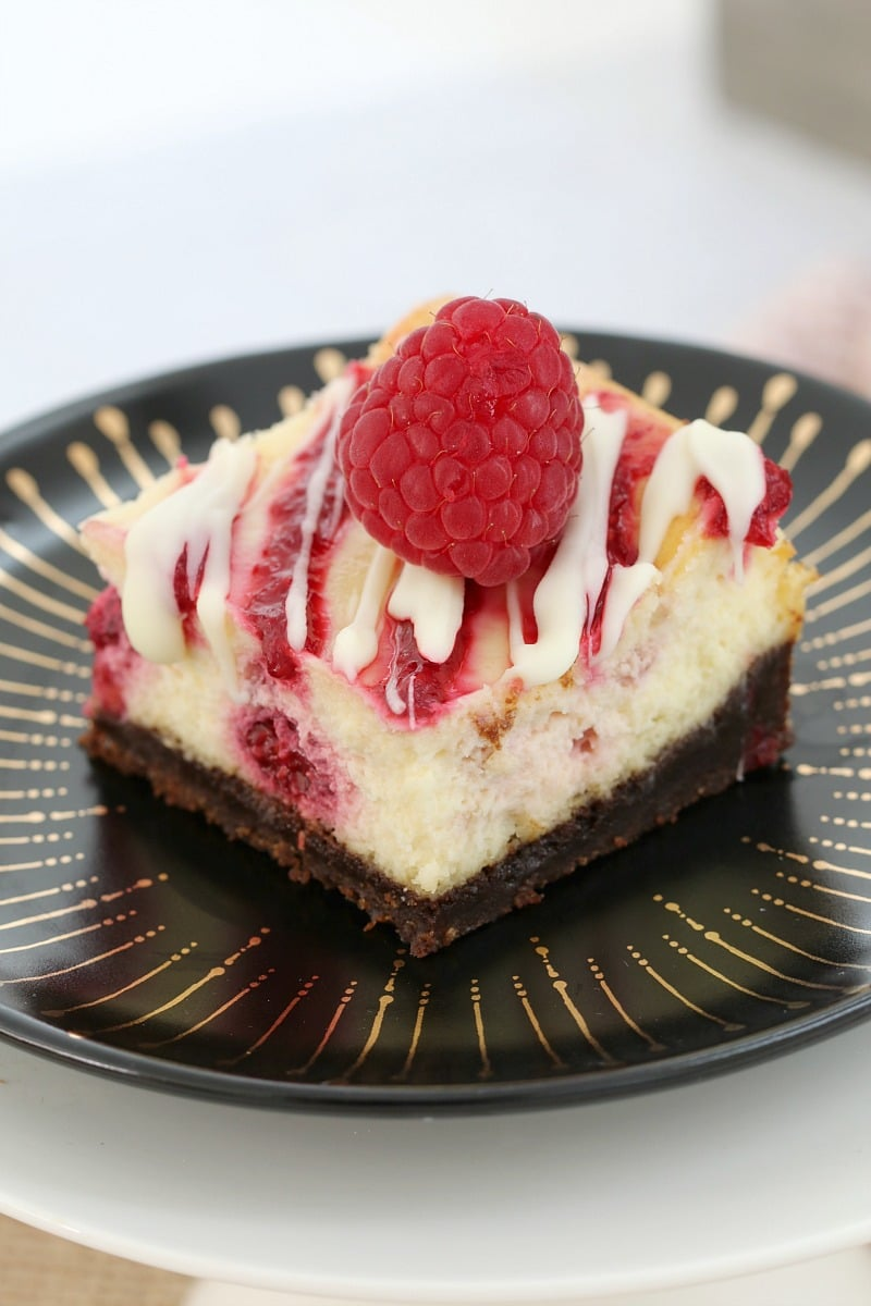 A square of cheesecake made with raspberries and white chocolate and topped with a fresh raspberry, served on a black plate