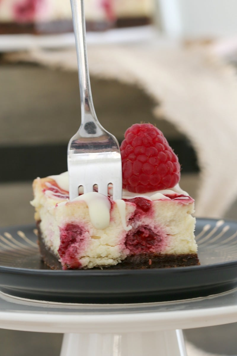 A plate with a fork standing up in a cheesecake square that has a fresh raspberry on top
