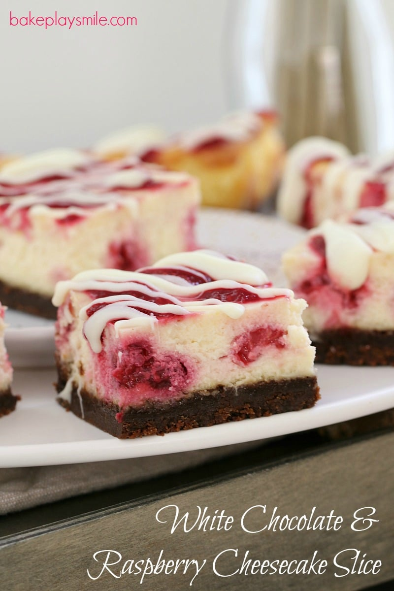 A close up of cheesecake squares made with a chocolate base, raspberries in the filling and white chocolate drizzled over the top