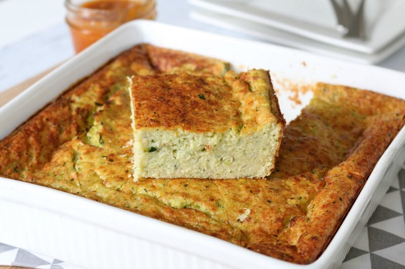 A baking dish filled with zuchinni slice with one piece cut and sitting on top to show texture