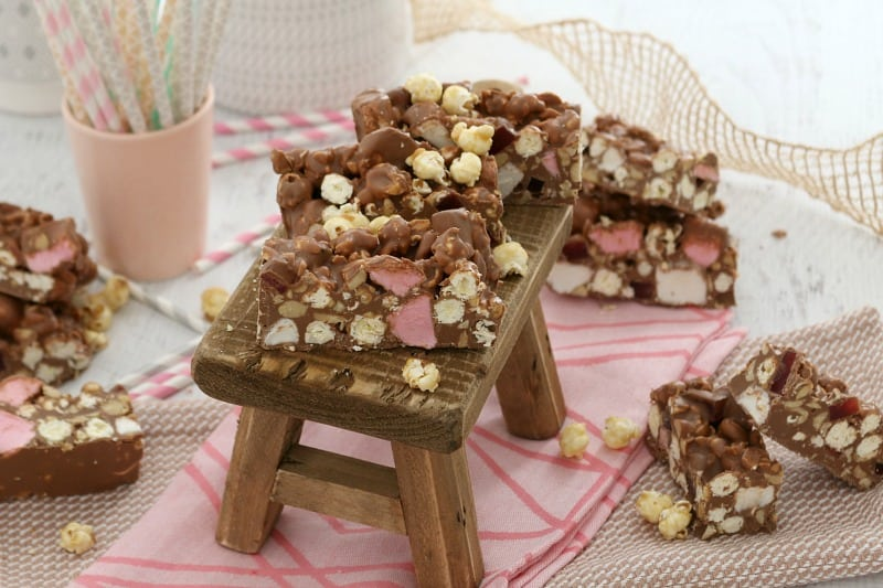 Pieces of Rocky Road filled with caramel popcorn, peanuts, marshmallows and Turkish Delight on a mini wooden stool