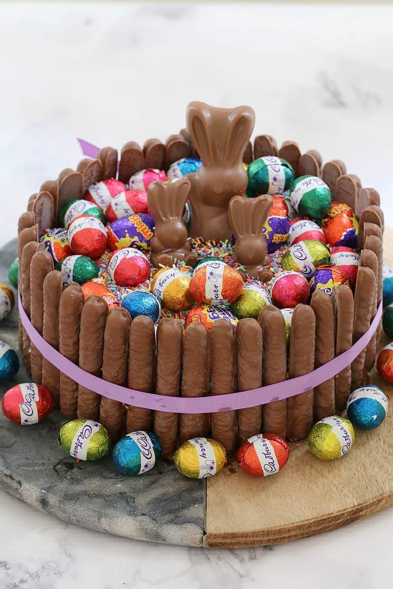 A round cake decorated with chocolate finger biscuits around the sides, topped with sprinkles, wrapped mini Easter eggs , and mini chocolate bunnies