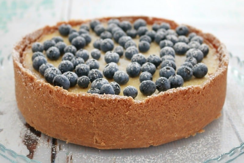 A baked lemon cheesecake with a crumb base and sides, decorated with fresh blueberries
