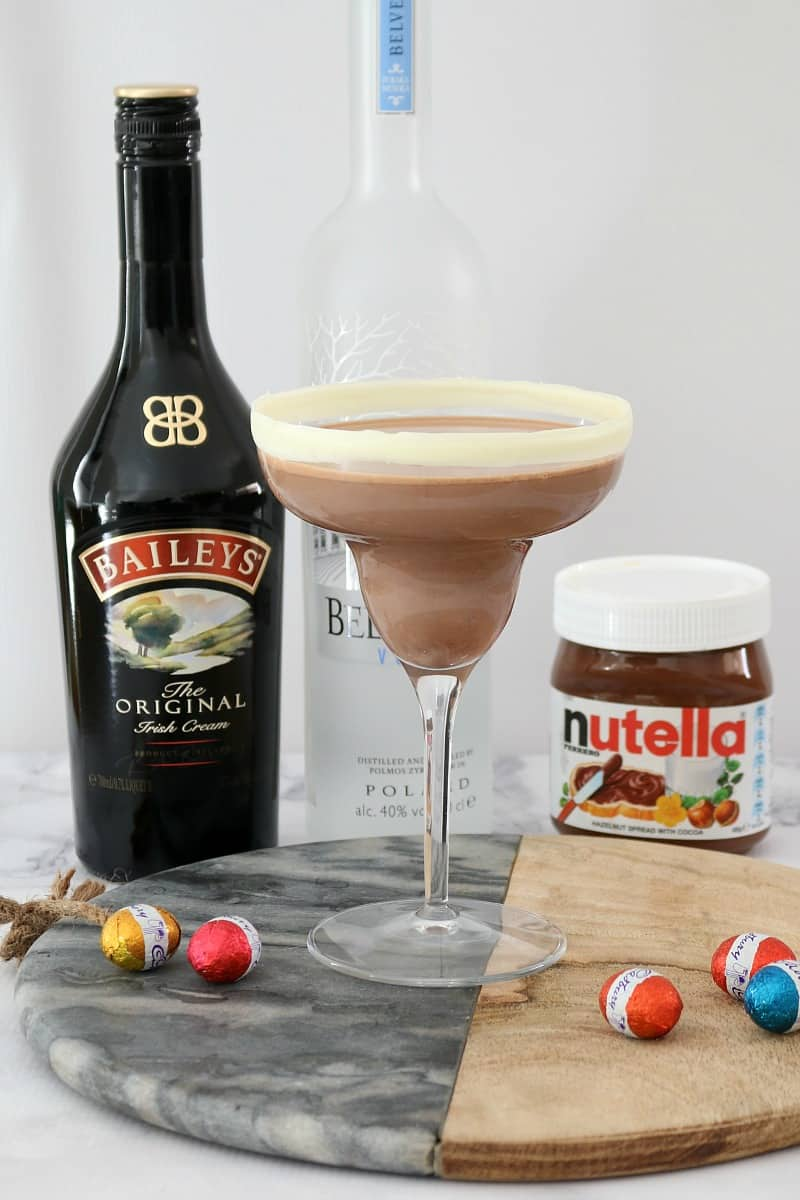 A bottle of vodka and Baileys, a tub of Nutella and solid easter eggs behind a cocktail.
