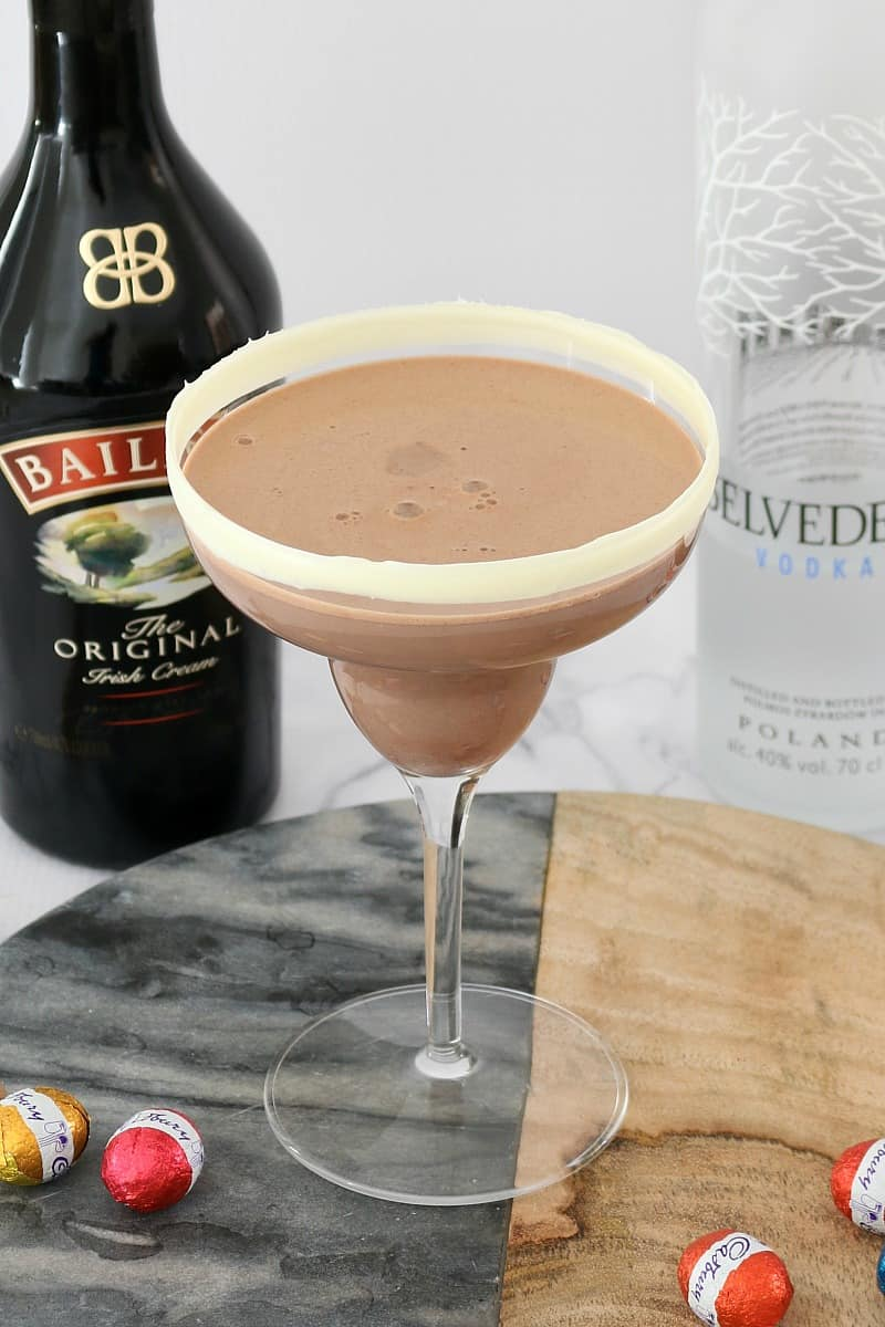 A cocktail glass filled with a chocolate cocktail in front of a bottle of Baileys and bottle of Vodka