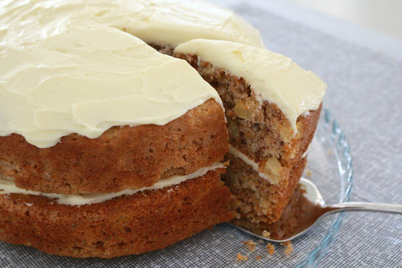 A wedge of layered carrot cake with frosting being removed from the cake