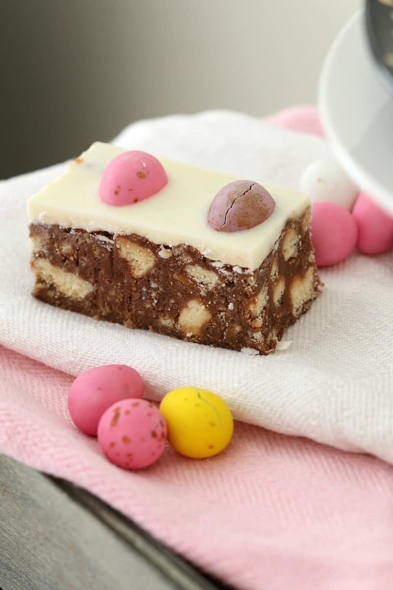 Purple and pink speckled mini easter eggs on a chocolate slice.
