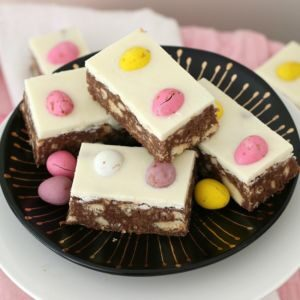 A plate of hedgehog slice decorated with white icing and pink and yellow sweets