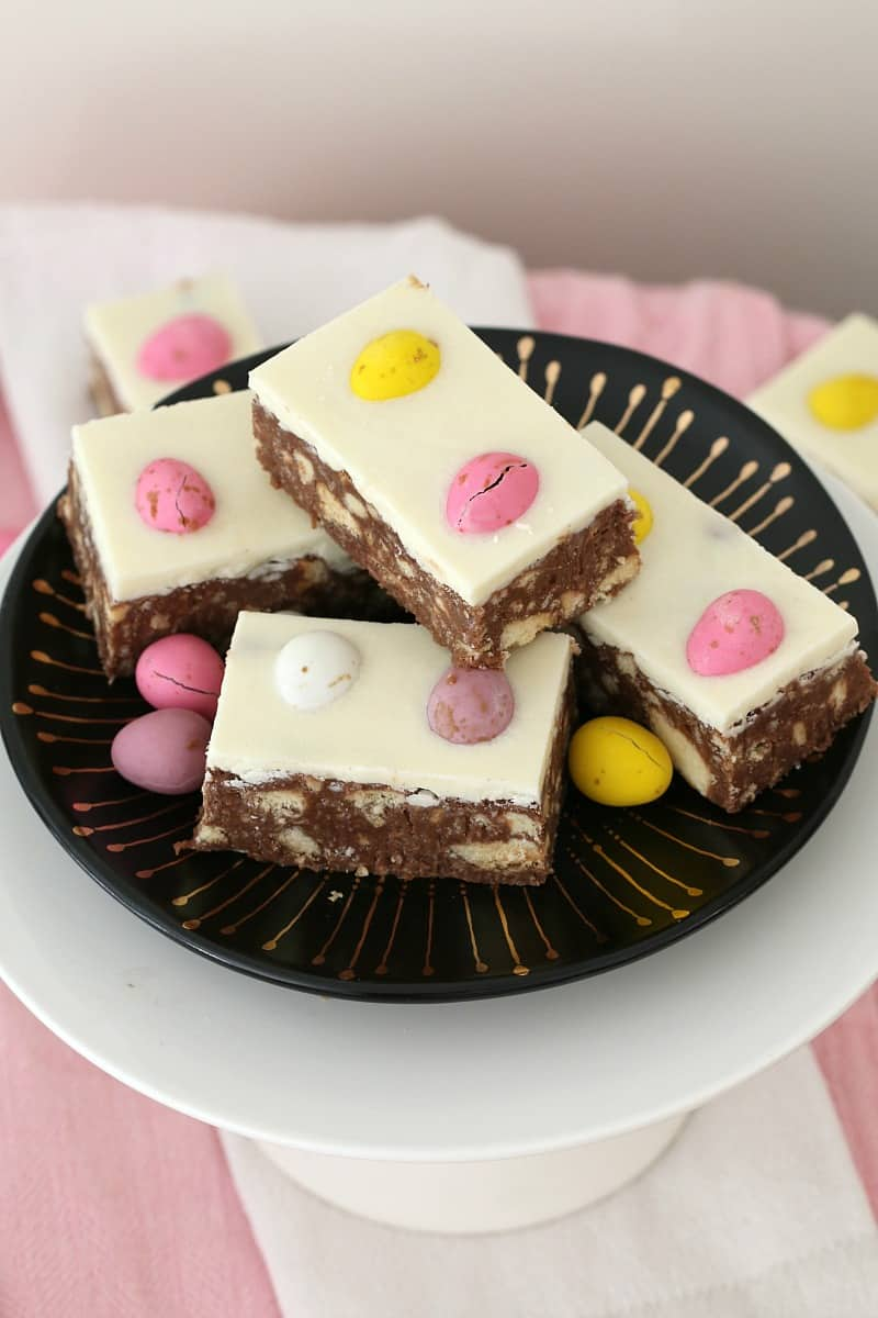 A hedgehog slice made with easter eggs on a black and gold plate.
