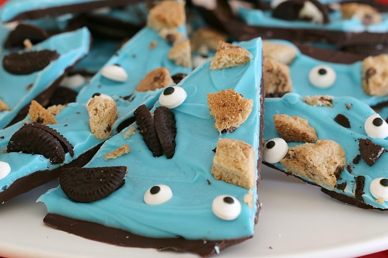 Wedges of chocolate bark topped with a layer of blue candy, and pieces of broken Oreo and choc chip biscuits, and edible eyes