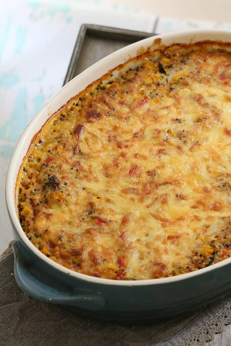 A baking dish filled with quinoa and vegetable bake topped with melted cheese