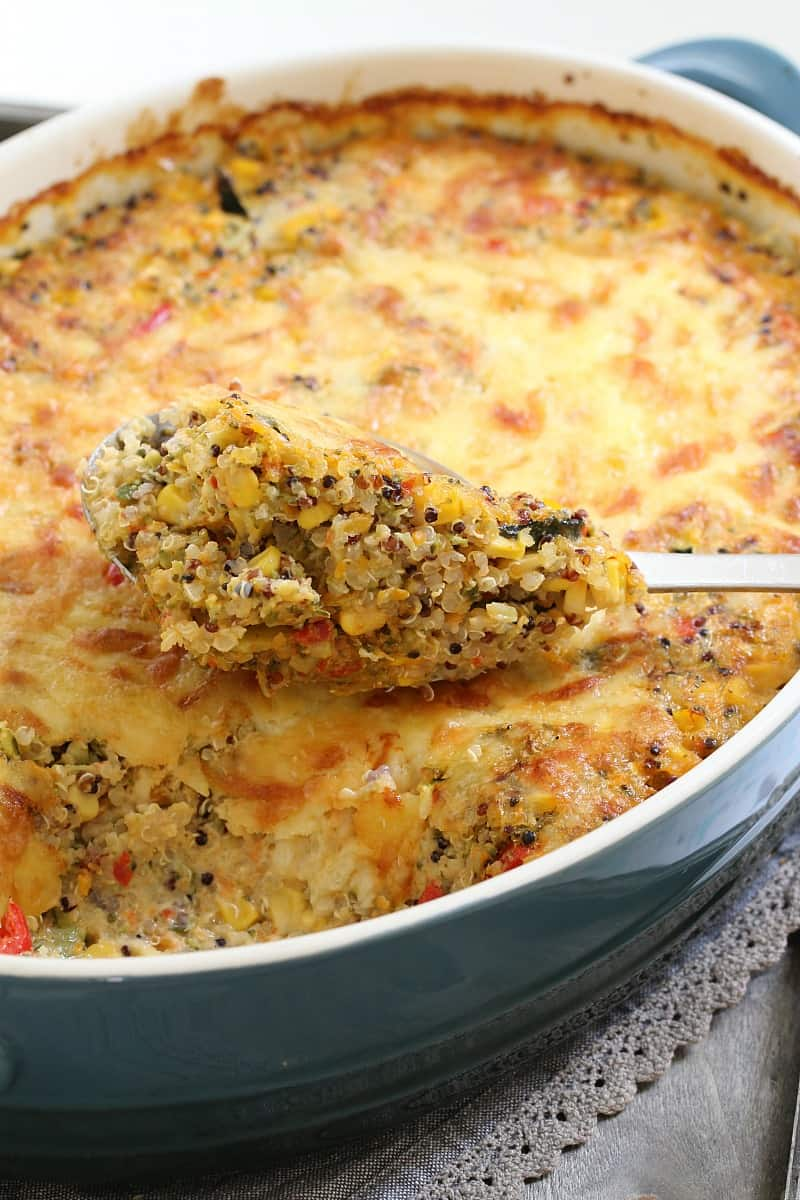 A baking dish and spoonful of a quinoa and vegetable bake, topped with melted cheese