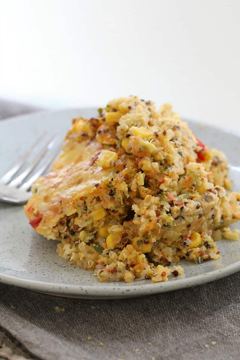 A serve of a quinoa, vegetable and cheese bake on a plate with a fork