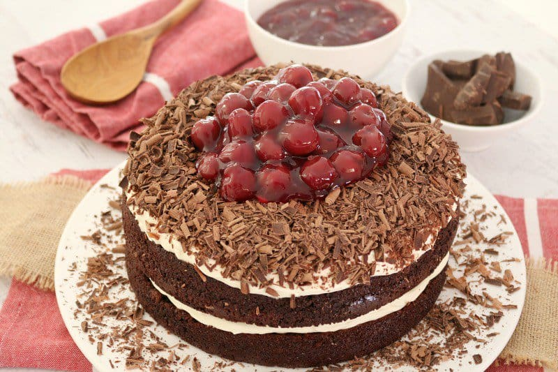 A round Black Forest chocolate cake layered with cream and topped with grated chocolate and morello cherries