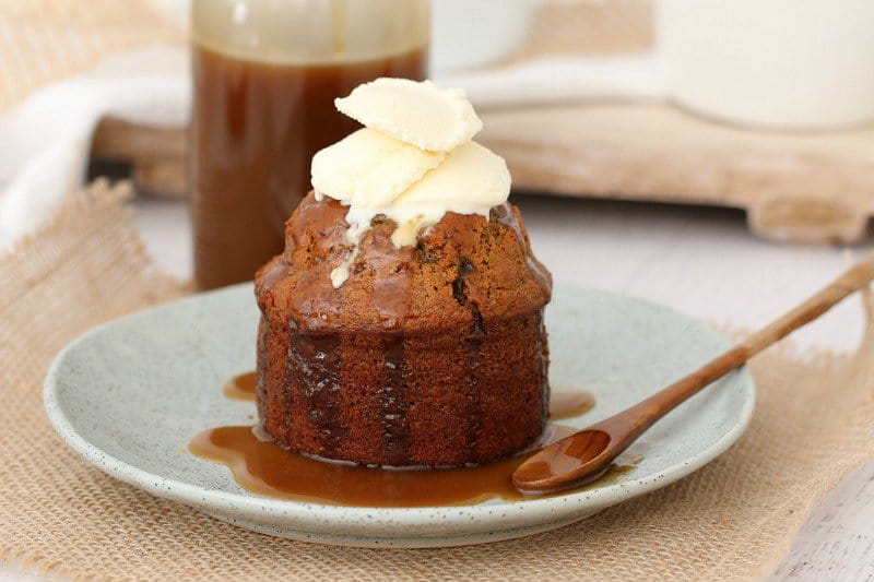 An individual sticky date pudding, drizzled with caramel sauce and topped with whipped cream, and served on a white plate