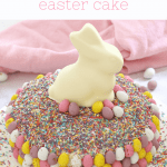 An Easter cake hack made with a white chocolate mud cake, sprinkles, Easter chocolate eggs and a bunny.