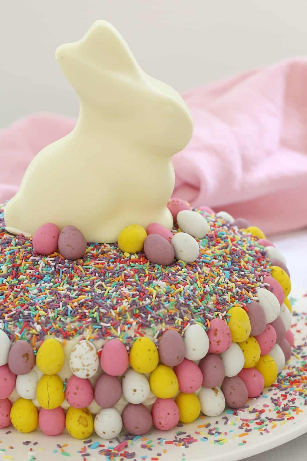Colourful chocolate easter eggs and sprinkles on a cake.