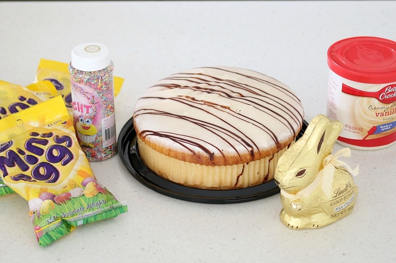 Packets of mini easter eggs, sprinkles, a mud cake, a Lindt bunny and a tub of frosting.