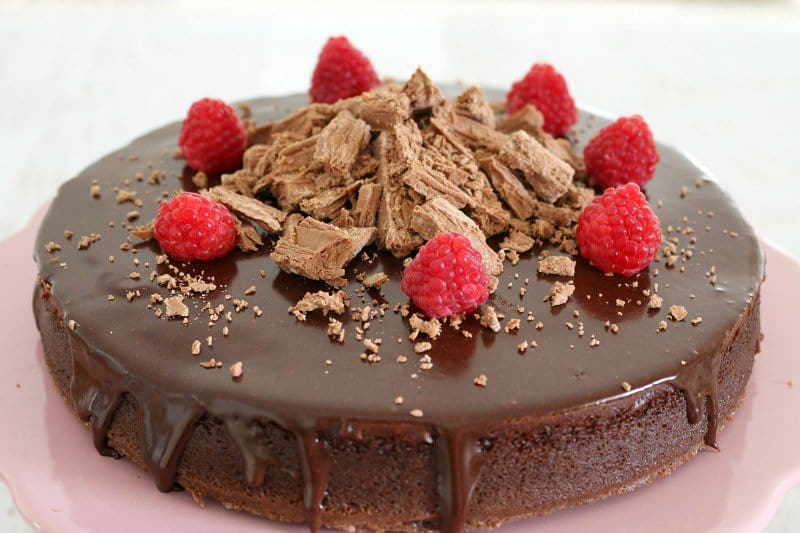 A round chocolate cake topped with a chocolate ganache, crumbled Flake and fresh raspberries