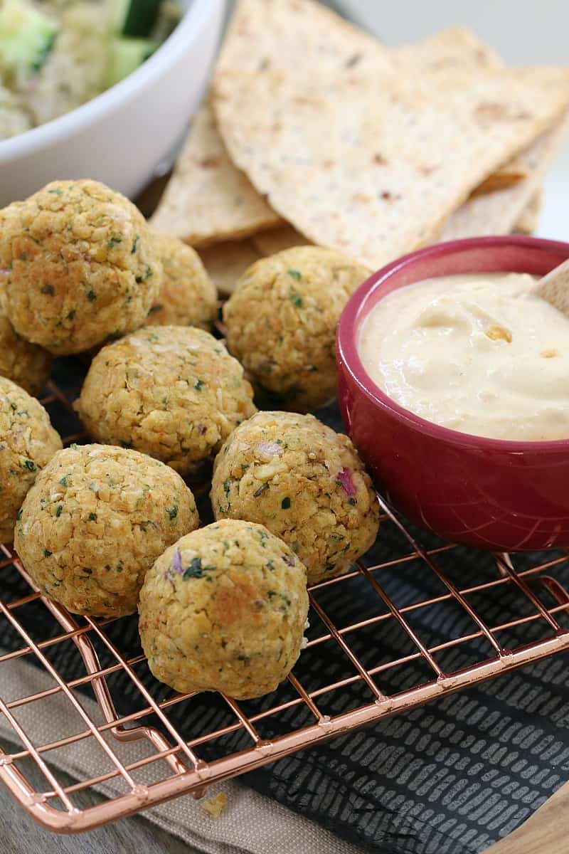 Falafel balls on a wire tray with a bowl of hommus and pita bread beside