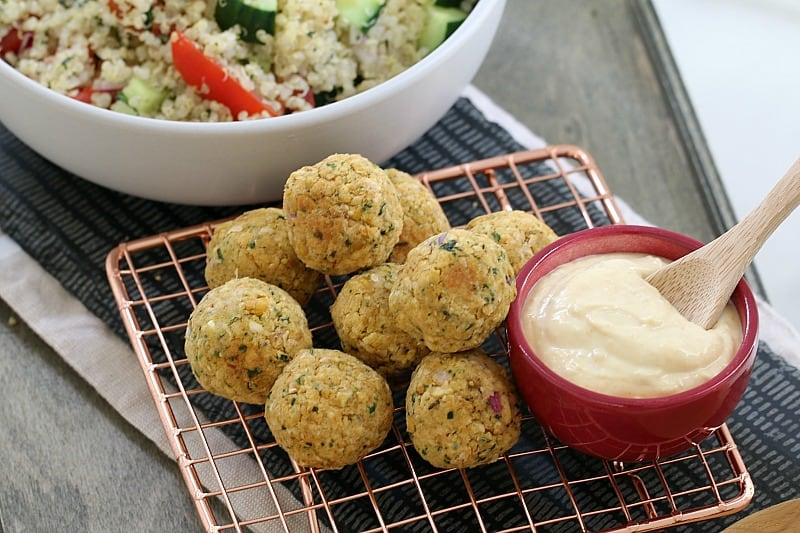 A pile of healthy falafel balls next to a bowl of hommus on a copper wire tray, and a quinoa salad behind
