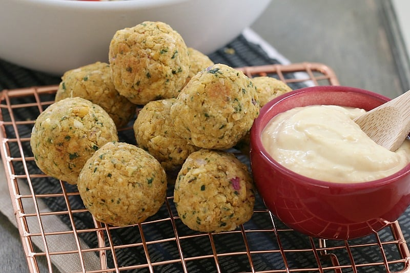 A close up of falafel balls piled up on a copper wire tray next to a bowl of hommus