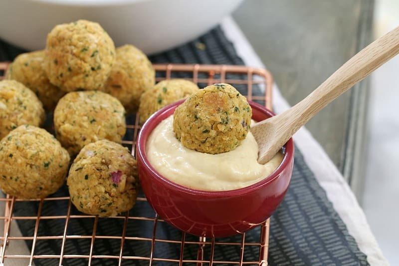 Falafel balls on a wire tray with one dipped into a bowl of hommus