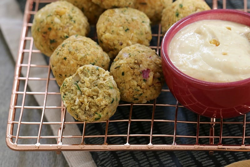 Falafel balls on a wire tray with one split open and a bowl of hommus beside
