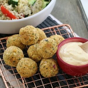 Healthy falafel balls piled on a copper wire tray with a bowl of hommus in front of a bowl of quinoa salad