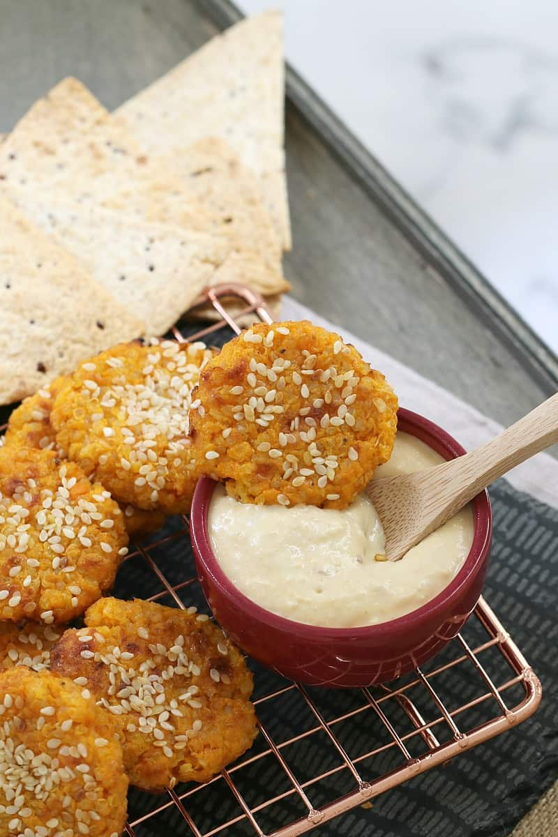 Healthy bites sprinkled with sesame seeds, with one dipped into a pot of hommus