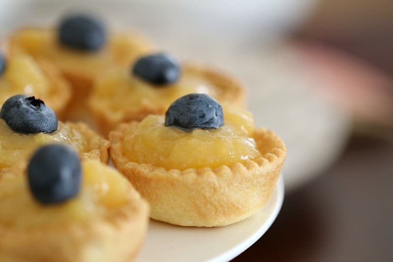 A close up of a plate of lemon tarts topped with blueberries